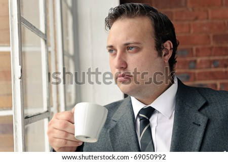 Old style man with coffee at the window while wearing suit