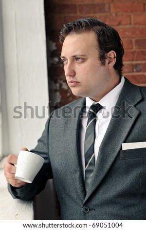 Old style man with coffee at the window while wearing suit - stock photo