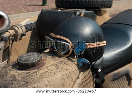 old-style motor helmet with a pair of sunglasses - stock photo