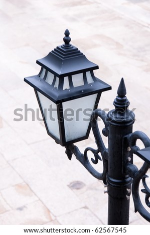 Old style new black lamp post  on a stone floor in the street