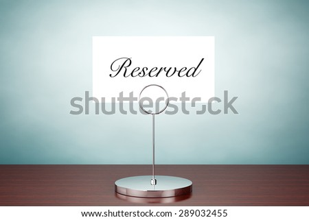 Old Style Photo. Note Paper Card Holder with Reserved Sign on the table - stock photo