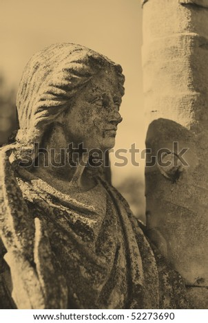 old style photo of angel statue in cemetery