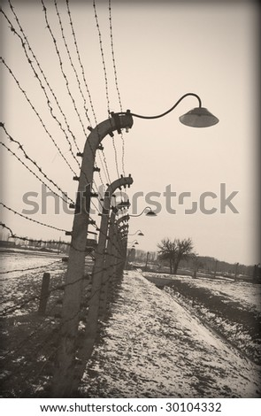 Old style photo of Auschwitz camp, electric fence - stock photo