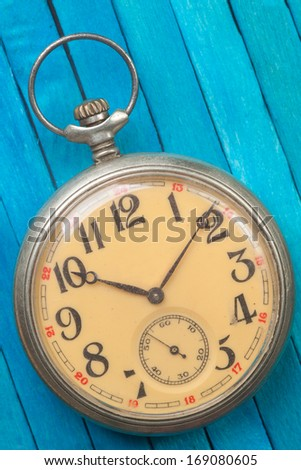 old style pocket watch on blue wooden background - stock photo