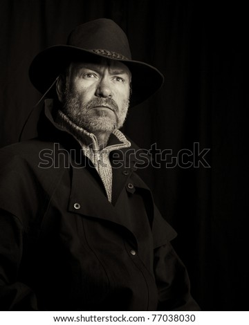 Old style portrait of a rugged looking cowboy - stock photo