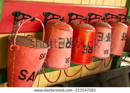 Old style red fire buckets on a train station.