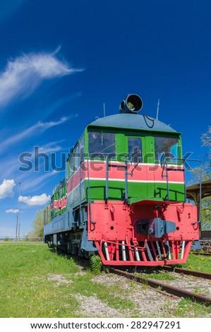 Old style retro locomotive train under blue sky - stock photo