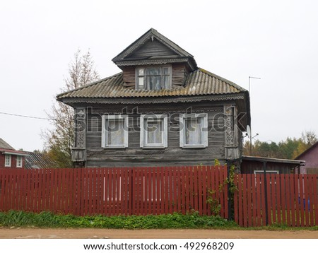 Old style Russian country house with carved windows and red wood plank fence.