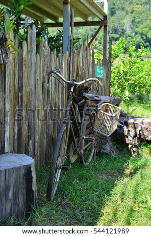 old style rusty brown bicycle and wood fence
