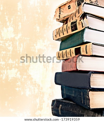 Old style stack of books on grunge background - stock photo