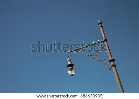 Old style street lantern with broken lamp isolated on blue sky background