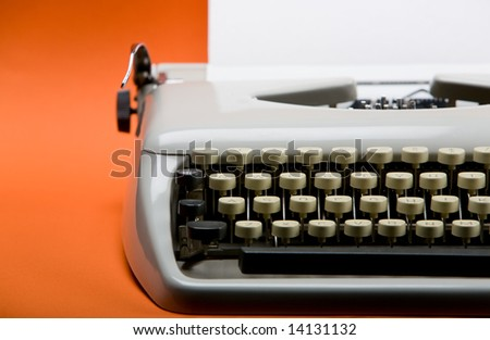 Old style typewriter with inserted blank paper over orange background - stock photo