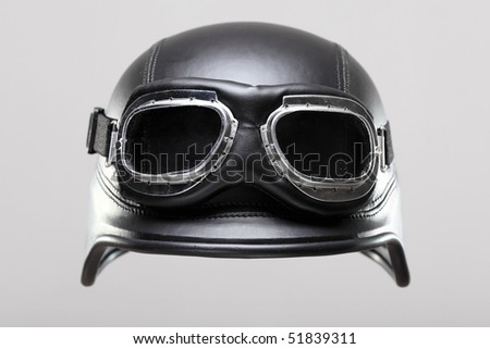 old-style us army motorcycle helmet with goggles, floating on gray background - stock photo