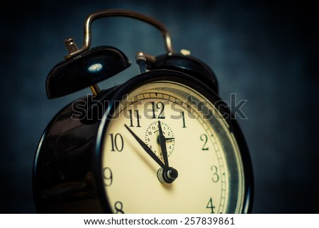 Old style vintage black metal alarm clock on dark blue background, close up vintage acid colored image