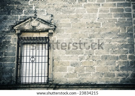 Old style window on creepy stonewall - stock photo