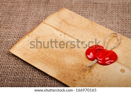 Old styled closed envelope with red sealing wax stamp, burlap background  - stock photo