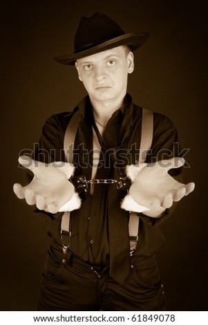 Old-styled photo of gangster in handcuffs