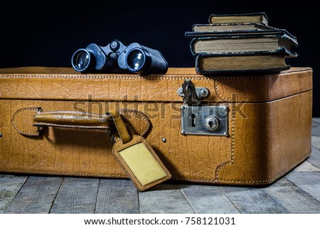 Old stylish suitcase. Old books in a suitcase. Suitcase on a wooden table. Black background
