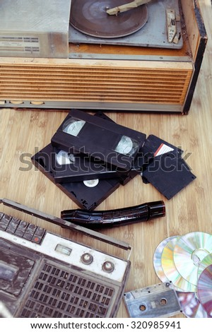 Old subjects of 70-90 years: a record player, video of the cartridge, disks, the cartridge and a film on a wooden background - stock photo