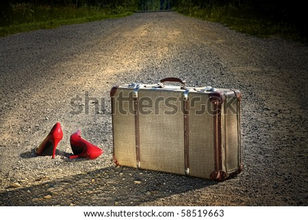 Old suitcase with red shoes left on dirt road - stock photo