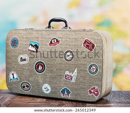 old suitcase with stikkers on the floor against the backdrop of a world map - stock photo