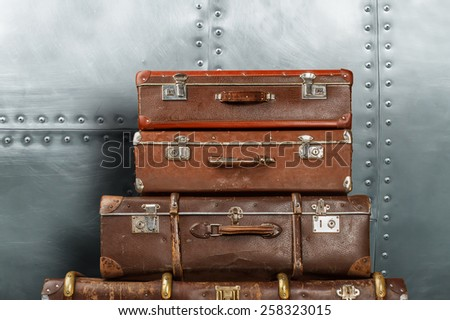 Old suitcases on metal wall background - stock photo