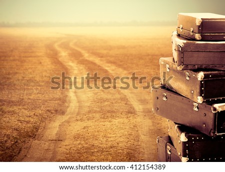 Old suitcases on the country road, lifestyle in retro style. Travel concept with vintage bags and roadside. Trip of the road with a baggage. Copy-space for your text, perspective view.