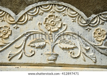 Old sunlit flowery wall ornament, India - stock photo