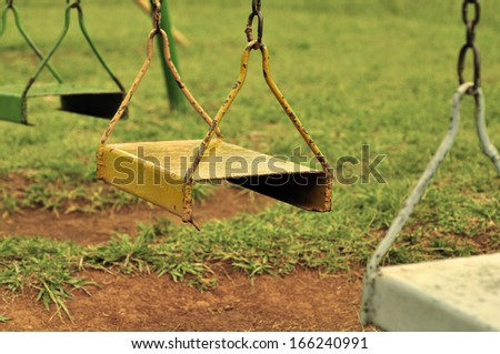 Old Swings on an Empty Playground, Vintage Look - stock photo