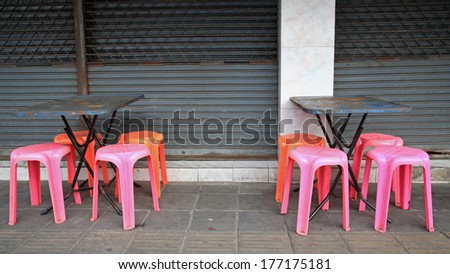 Old tables and plastic chairs at Thai footpath restaurant - stock photo