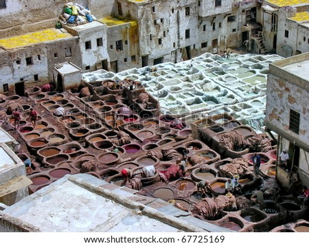 Old tannery in Moroccan Medina. - stock photo