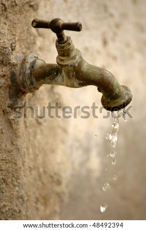 Old tap dripping on a blurred background. reduced depth of field, focus on the dripping water - stock photo