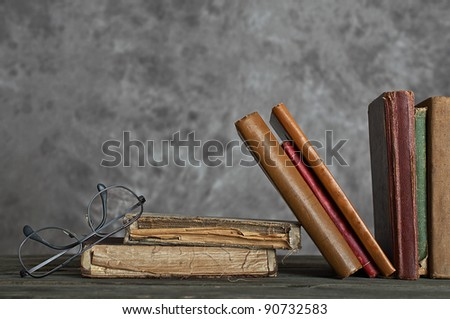 old tattered  books with reading glasses