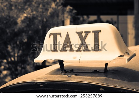 Old taxi sign on the Thailand's Tuk-Tuk roof - stock photo