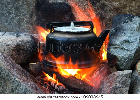 Old teapot boils on campfires - stock photo