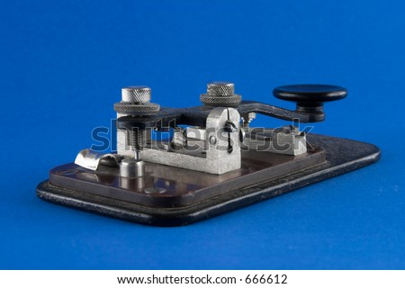 Old telegraph key over blue background - stock photo