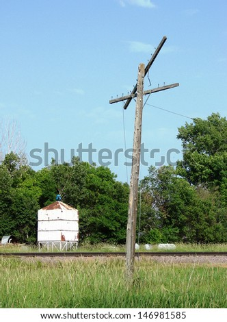 old telegraph pole by railroad tracks - stock photo