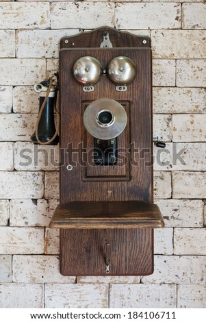 old telephone hanging on brick wall - stock photo