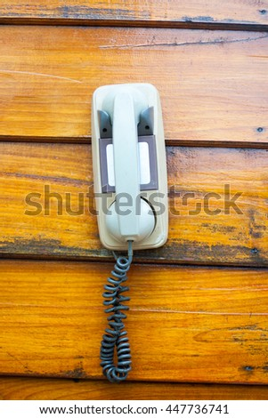Old telephone hanging on wooden background. - stock photo