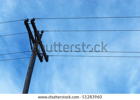 old telephone pole silhouetted against blue sky, copy space in lower right - stock photo