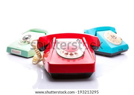 Old telephones on white - stock photo
