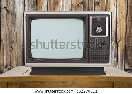 Old television and table with rustic wood wall. - stock photo