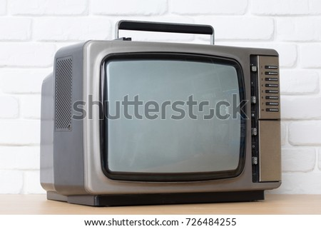 Old television on a white brick wall background.