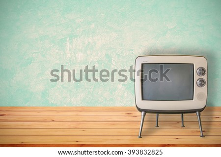 Old television on wood table. Vintage color tone style. - stock photo