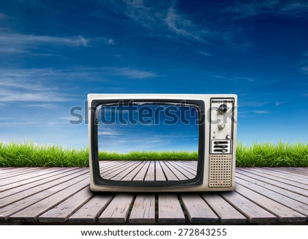 old television on wooden terrace with fresh spring green grass and blue sky - stock photo