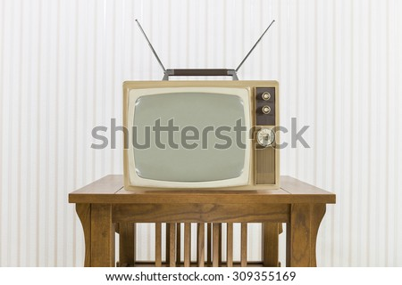 Old television with antenna on wood table. - stock photo