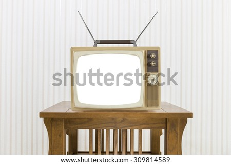 Old television with antenna on wood table with cut out screen. - stock photo