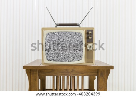 Old television with antenna on wood table with static screen. - stock photo