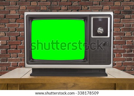 Old television with chroma key green screen and brick wall. - stock photo