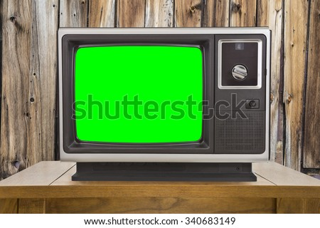 Old television with chroma key green screen and rustic wood wall. - stock photo